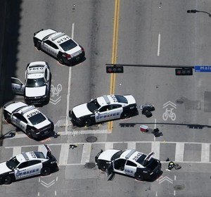 Police cars remain parked at the crime scene of a shooting attack in downtown Dallas. REUTERS/Brandon Wade