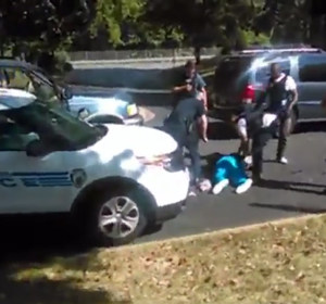 Keith Lamont Scott lies on the ground while officer approach him after shooting