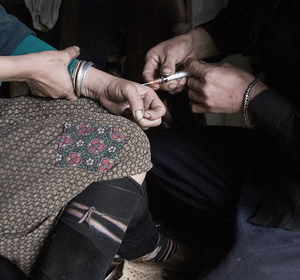 A man injecting heroin into a woman's hand.