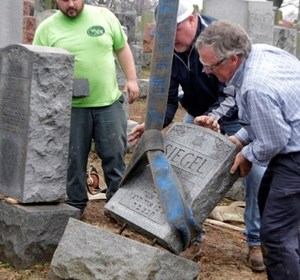 Three men from Weiss and Rosenbloom Monument company work to right toppled headstones. REUTERS/Tom Gannam