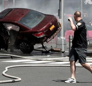 A man walks past a crashed car in Times Square, New York. REUTERS/Mike Segar