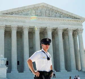 A policeman stands outside of the Supreme Court building following a case involving Trinity Lutheran Church. REUTERS/Yuri Gripas.
