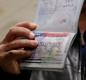 A member of the Al Murisi family shows the cancelled visa in their passport. REUTERS/Jonathan Ernst/Files