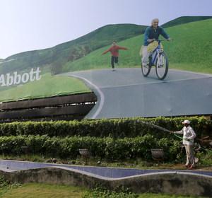 A worker waters plants next to an advertisement billboard of Abbott in Mumbai, India, November 12, 2015. REUTERS/Danish Siddiqui