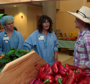 Amanda Sweetman, project manager, The Farm, talks with two Registered Nurses. REUTERS/Rebecca Cook