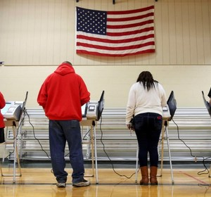 Voters casting their votes. REUTERS/Aaron Josefczyk