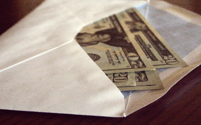 $20 bills sit inside an envelope