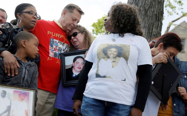 Father Michael Pfleger comforts a woman during a May news conference by a group of mothers who lost children to gun violence. REUTERS/Jim Young