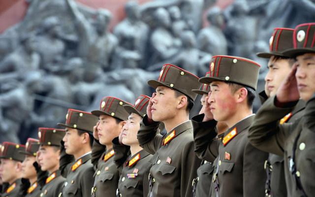 North Korean soldiers salute unpictured bronze statues. Kyodo/via REUTERS