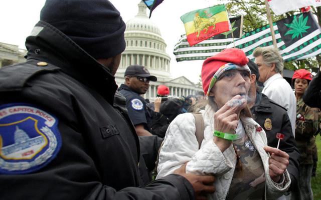 Police officers arrest protesters smoking marijuana on steps of the U.S. Capitol. REUTERS/Yuri Gripas
