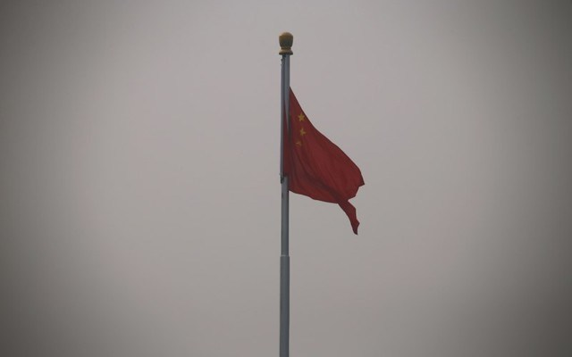 A Chinese flag waves against a gray sky. REUTERS/Petar Kujundzic.