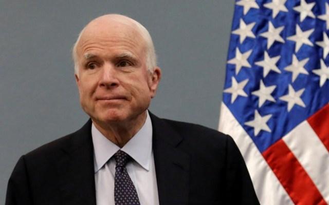 Senator John McCain poses in front of an American flag. REUTERS/Henry Romero