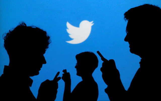 An illustration of people holding phones against a Twitter-logo backdrop. REUTERS/Kacper Pempel/Illustration/File Photo