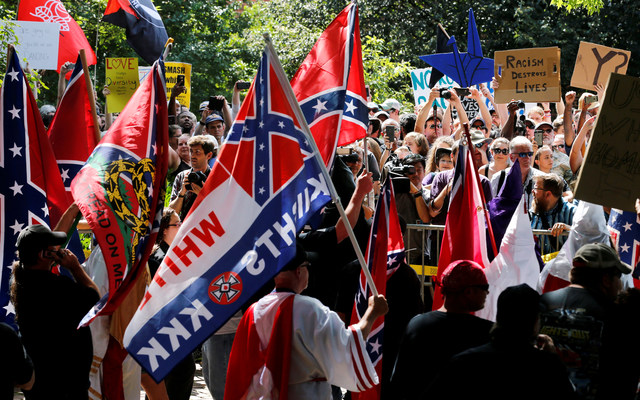 Members of the Ku Klux Klan face counter-protesters as they rally in support of Confederate monuments in Charlottesville, Virginia, U.S. on July 8, 2017. REUTERS/Jonathan Ernst