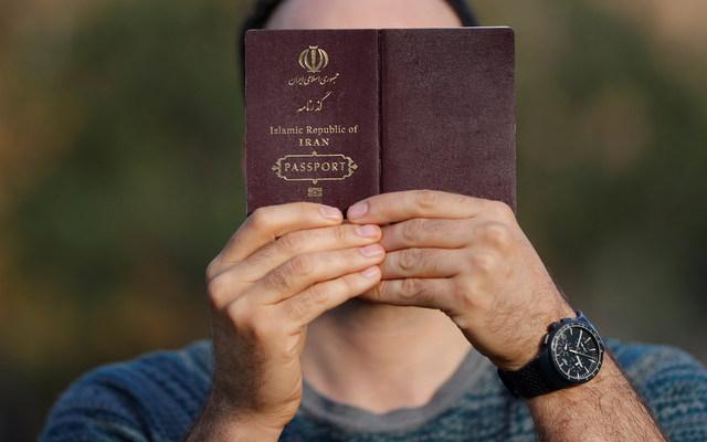 An Iranian refugee holds his passport.