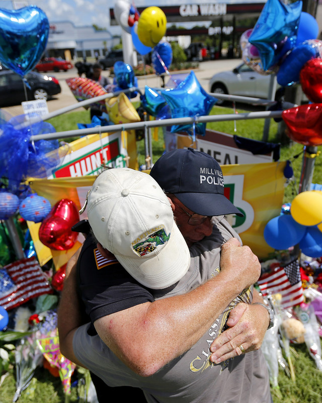 Mourners embrace at a Baton Rouge lawn memorial. REUTERS/Jonathan Bachman