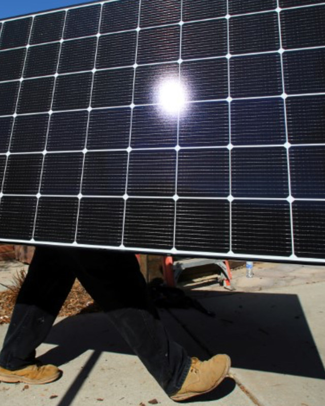 A solar installer carries a solar panel. REUTERS/Mike Blake