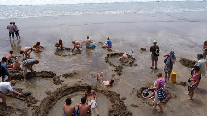 A group of people, digging on the beach