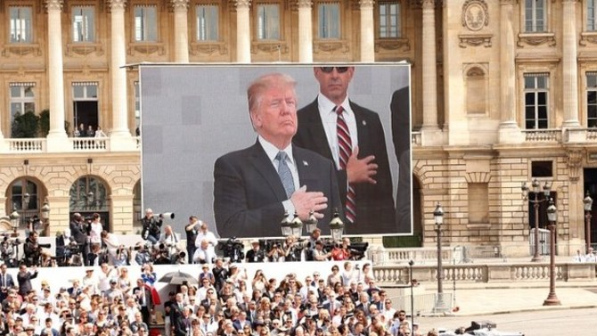 President Trump's image is projected onto a screen at a Bastille Day celebration in Place de la Concorde, Paris. REUTERS/Kevin Lamarque