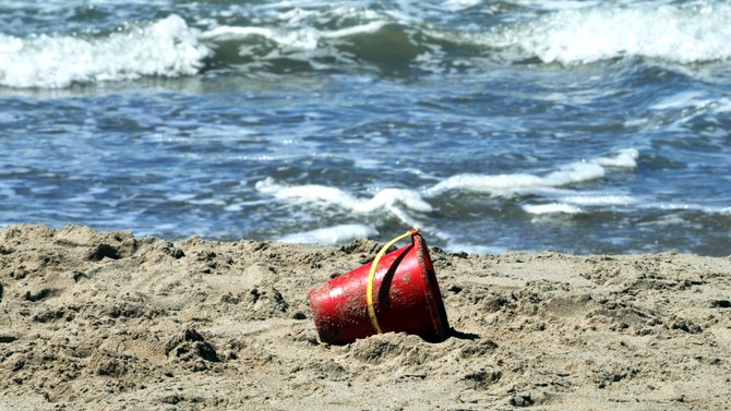 A red toy bucket toppled over at the beach.